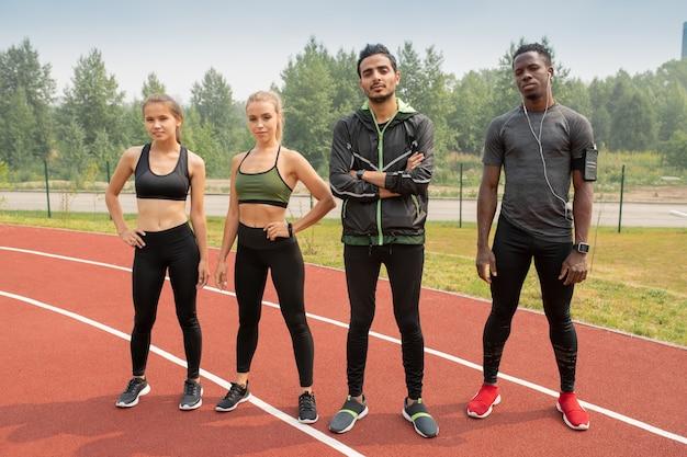 Reihe junger interkultureller athleten in sportbekleidung, die vor dem marathon auf rennstrecken des freiluftstadions stehen