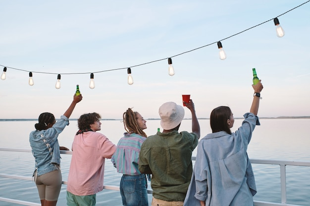 Reihe junger interkultureller ekstatischer freunde, die getränke auf dem pier trinken