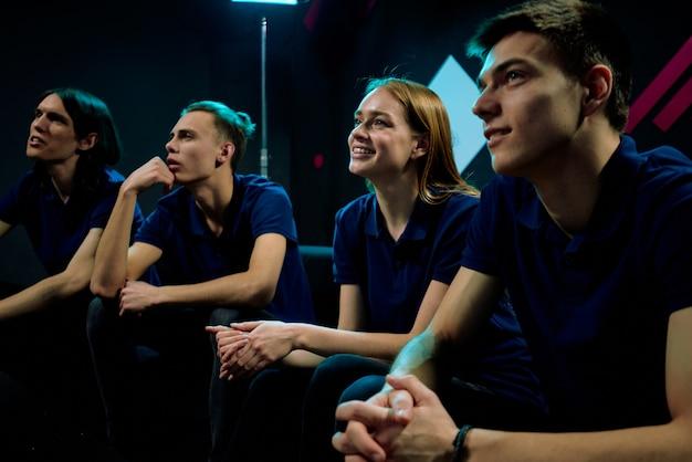 Reihe mehrerer junger zeitgenössischer e-sport-videospieler, die sich auf einer konferenz die online-präsentation eines neuen netzwerkspiels ansehen