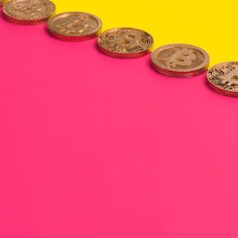 Reihe vieler bitcoins über dem gelben und rosa doppelhintergrund