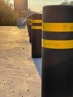 Reihe von antiparkpollern auf dem bürgersteig bei sonnenuntergang