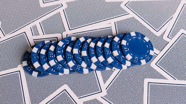 Reihe von blauen pokerchips auf spielkarten