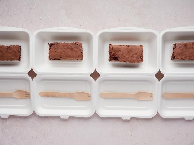 Reihe von brownie-behältern mit holzlöffel zur auslieferung bereit
