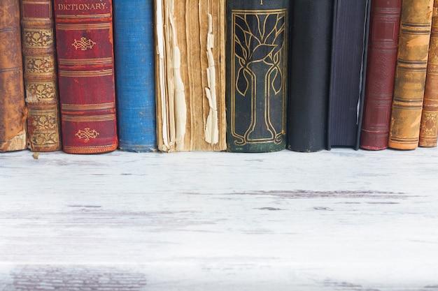 Reihe von büchern auf weißem hölzernem schreibtisch