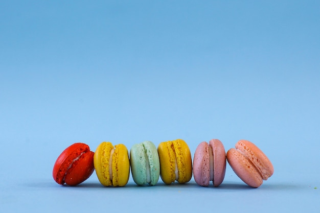 Reihe von bunten macarons auf blauem hintergrund
