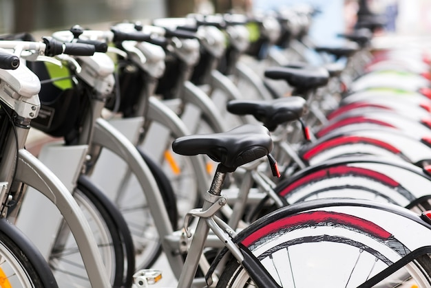 Reihe von geparkten weinlesefahrrädern fährt für miete auf bürgersteig rad