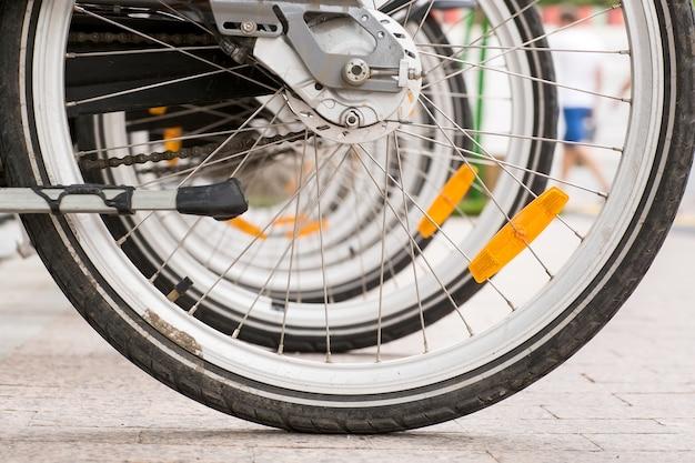 Reihe von geparkten weinlesefahrrädern fährt für miete auf bürgersteig rad.