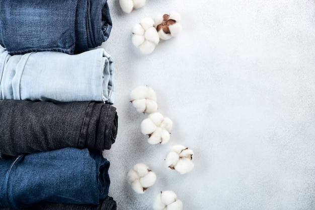Reihe von gerollten jeans und baumwollblumen auf hellem hintergrund