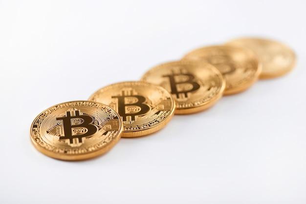 Reihe von glänzenden goldenen bitcoins als weltgrößte kryptowährung lokalisiert auf weißem hintergrund.