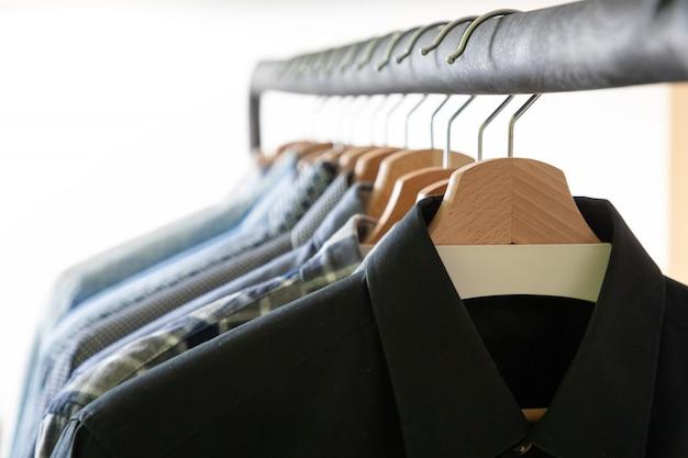 Reihe von herrenhemden in blauen farben auf kleiderbügel