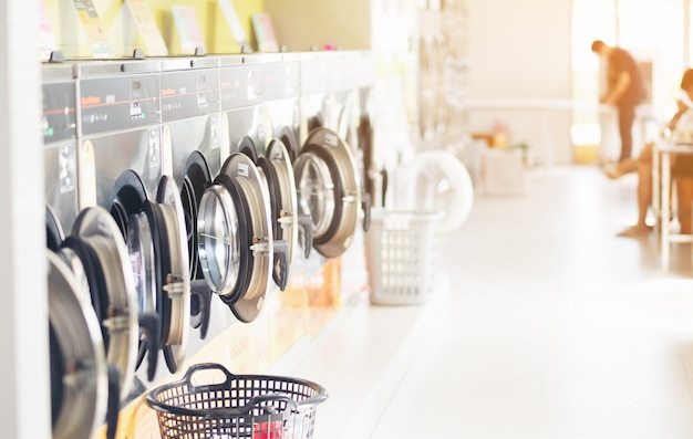 Reihe von industriellen wäschereimaschinen im waschsalon in einem allgemeinen waschsalon, mit wäscherei in einem korb, thailand
