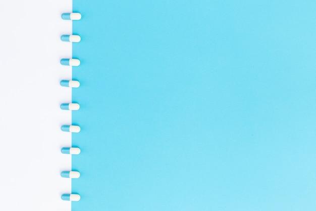 Reihe von kapseln auf weißem und blauem doppelhintergrund
