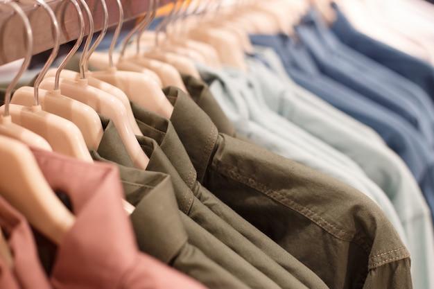 Reihe von kleiderbügeln mit hemden in einem speicher