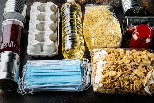 Reihe von lebensmitteln. nahrungsmittelversorgung. spenden-, coronavirus- und quarantänekonzept auf altem dunklem tisch
