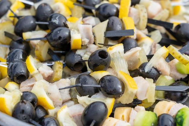 Reihe von leckeren häppchen, nahaufnahme. viele häppchen mit schwarzen oliven, gurken, zitrone, fett und fleisch auf einem teller