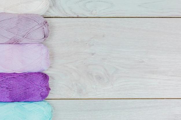 Reihe von lila; blaues und weißes strickgarn auf grauem hölzernem hintergrund