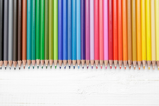 Reihe von mehreren buntstiften auf einem alten weißen holztisch aus holz Premium Fotos