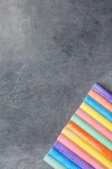 Reihe von mehrfarbigen kreidestiften auf dunklem steintafel-hintergrund.