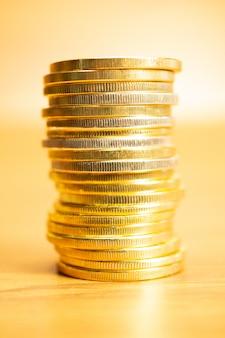 Reihe von münzen auf holztisch, vorderansichtbild der vertikalen ausrichtung mit selektivem fokus