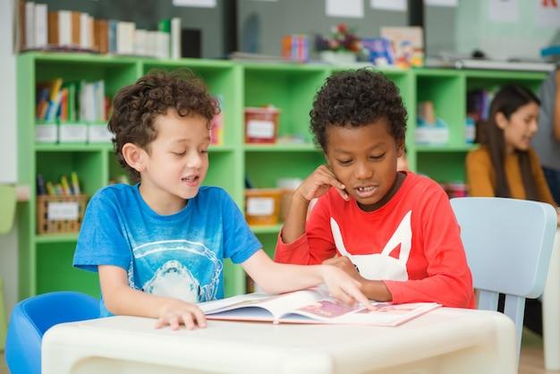 Reihe von multiethnischen elementarstudenten lesung buch im klassenzimmer. vintage effekt stil bilder.
