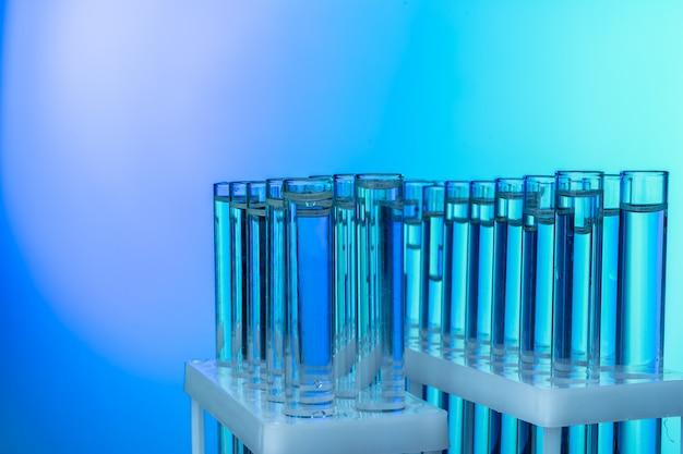 Reihe von reagenzgläsern mit flüssigkeiten auf blauem und grünem getontem hintergrund
