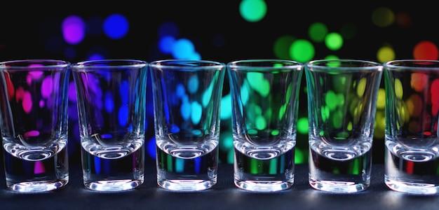 Reihe von sauberen, glänzenden gläsern, die auf einer bartheke in einem nachtclub aufgereiht sind, bereit für die barkeeper, um alkoholische getränke zu servieren