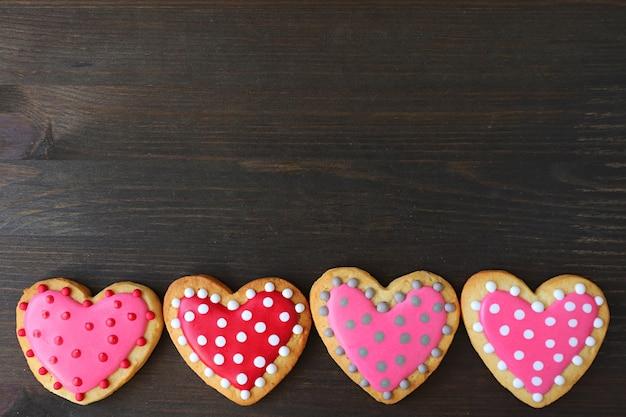 Reihe von schönen herzförmigen polka dots royal icing cookies auf schwarzem holzhintergrund