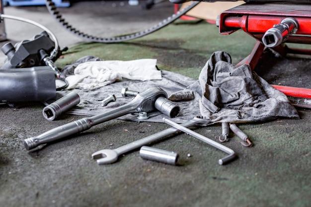 Reihe von schrauben- und schlüsselwerkzeugen auf einem boden in der werkstatt reparierte nahe alte fahrrad- oder motorradmaschine. industrieszene mit equipment