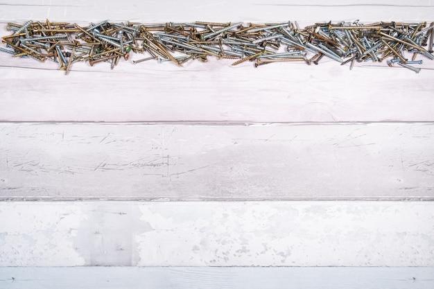 Reihe von schrauben verschiedener formen an der spitze eines freien raumes auf hölzernem hintergrund. draufsicht mit platz für text