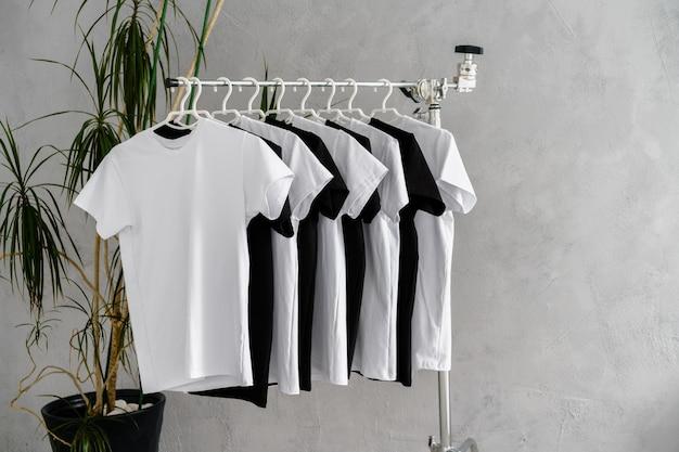 Reihe von schwarzen und weißen t-shirts, die am regal hängen, nahaufnahme