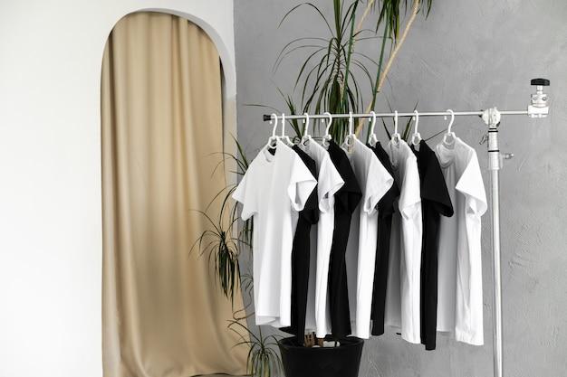 Reihe von schwarzen und weißen t-shirts, die am regal hängen