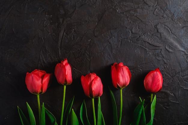 Reihe von tulpenblumen auf strukturiertem schwarzem hintergrund, kopierraum der draufsicht