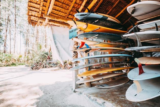 Reihe von verschiedenen bunten surfbretter in einem stapel zur miete am strand. vintage farbton-effekt.