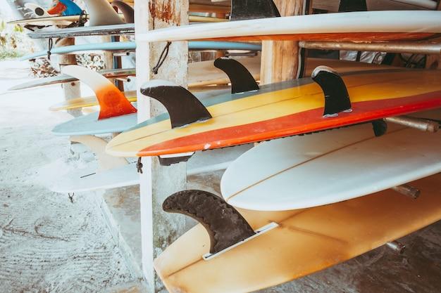 Reihe von verschiedenen bunten surfbretter in einem stapel zur miete am strand.