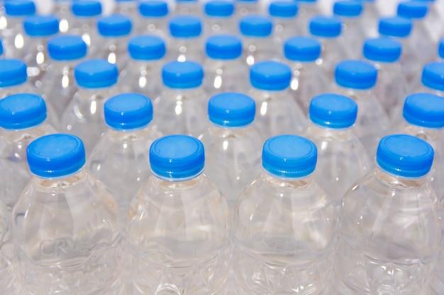 Reihe von wasserflaschen. flaschen mit blauen kappen für trinkwasser