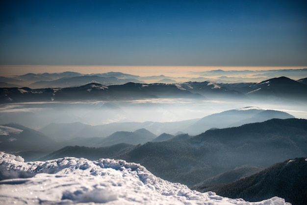 Reihe von winterbergen im weißen schnee nachts unter dunkelblauem himmel mit mond und sternen