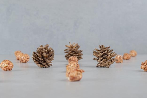 Reihen aromatisierter popcorns, die sich auf einige tannenzapfen auf dem marmortisch konzentrieren.