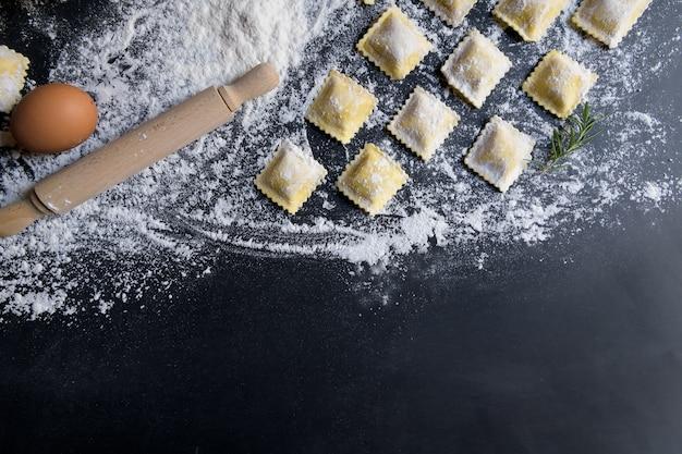 Reihen der rohen selbst gemachten ravioli mit bestandteilen