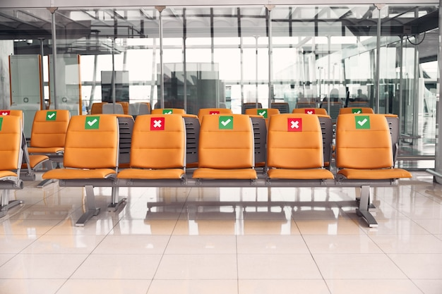 Reihen leere orangefarbene stühle, die anzeigen, wo sie sitzen können, um eine entfernung sicheres reisen neu normal zu halten