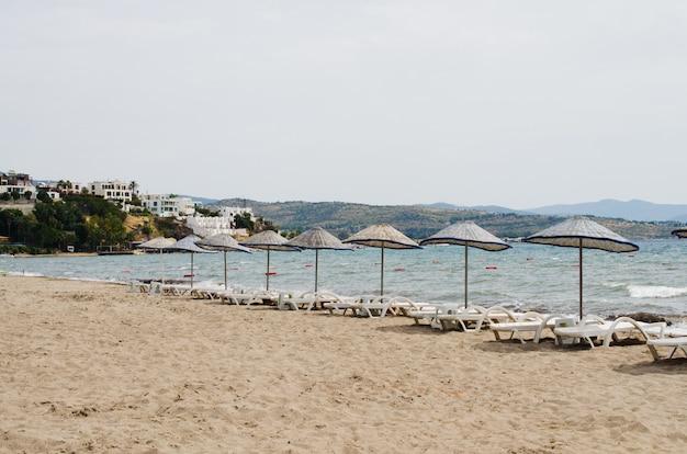 Reihen leerer sonnenliegen und sonnenschirme am strand. kamelstrand in der türkei.
