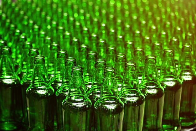 Reihen neuer leerer grüner glasflaschen. auf der produktionslinie. industrielle bierherstellung