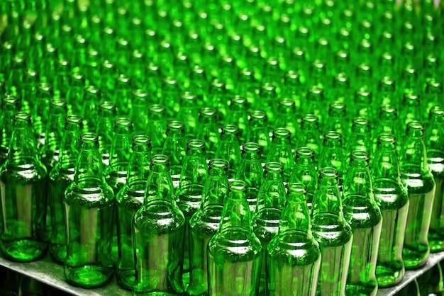 Reihen neuer leerer grüner glasflaschen. auf der produktionslinie.
