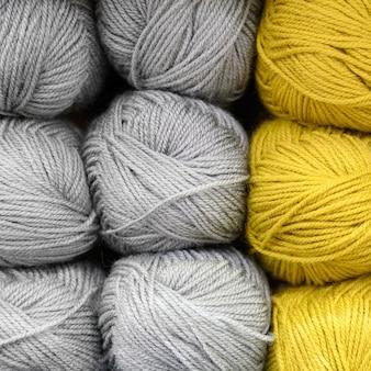 Reihen stränge aus flauschigem wollgarn zum stricken von weichen grauen und gelben farben. platz