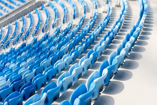 Reihen von blauen sitzen am fußballstadion.