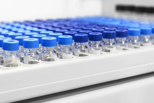Reihen von glasfläschchen im automatischen flüssigkeitsspender mit tablett. chemische laborgeräte. geringe schärfentiefe