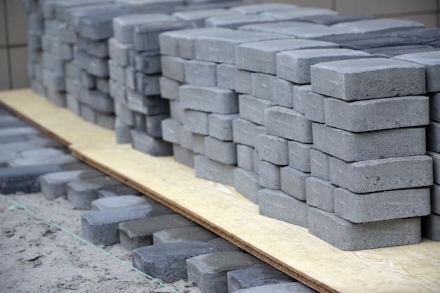 Reihen von grauer und dunkelgrauer gehwegplatte, die draußen liegen. material für die pflasterung von platten durch mosaik in bearbeitung