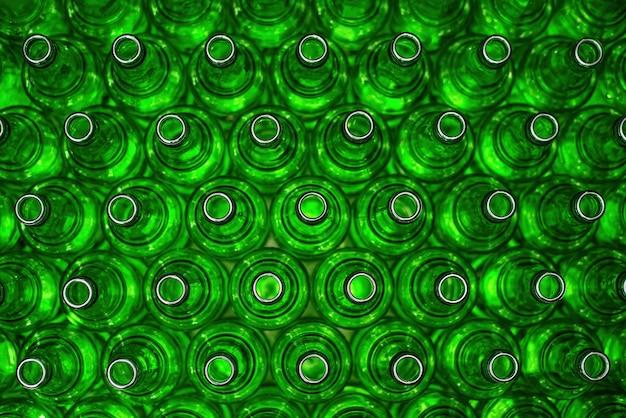 Reihen von grünen glasflaschen auf der nahaufnahme des förderers. industriebrauerei