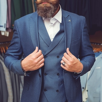 Reihen von herrenanzugjacken auf kleiderbügeln. bärtiger mann im anzug. mode und schönheit, geschäfts- und bürokleidung, jugend, muskulös und gesund, einkaufen und garderobe, chef und angestellter, mann im hemd, kopierraum