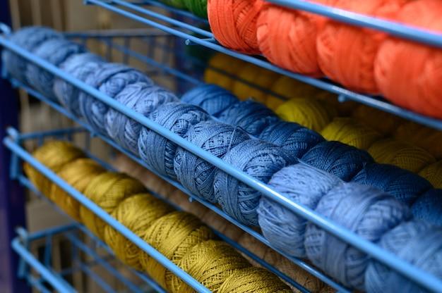 Reihen von kugeln aus bunten baumwollgarnfäden zum stricken von blauen, roten und senffarbenen farben in den regalen im laden
