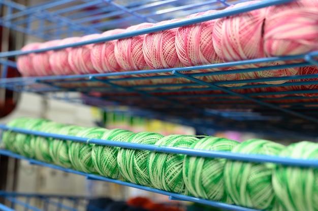Reihen von kugeln aus bunten baumwollgarnfäden zum stricken von meliert gestreiften rosa und grün-weißen farben in den regalen im laden